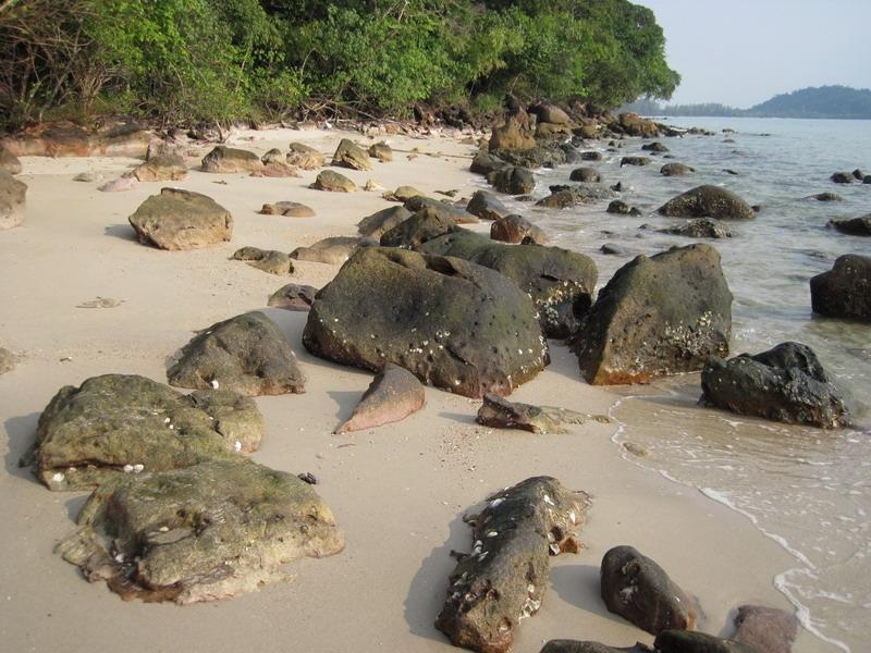 แนวหาดทรายที่น้ำลดลงพอเดินสะดวก สลับก้อนหินและโขดหิน